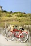 Bici che si appoggia contro la rete fissa alla spiaggia. immagini stock