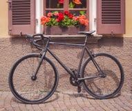 Bici colocada debajo de una ventana por completo de flores fotografía de archivo