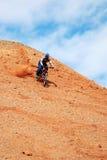 Bici cuesta abajo en la colina roja Imagen de archivo