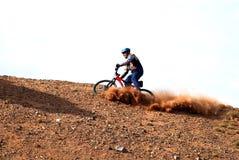 Bici cuesta abajo en la colina roja Fotos de archivo