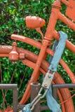 Bici d'annata bloccata e completamente dipinta in arancia fotografia stock