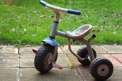 Bici d'annata delle ruote del triciclo tre del bambino nel giardino fotografie stock libere da diritti