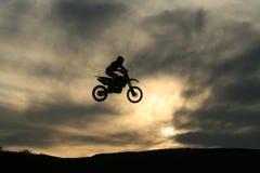 Bici de la suciedad silueteada contra las nubes de la puesta del sol Fotografía de archivo libre de regalías