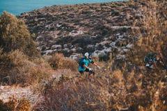 Bici de montaña, abajo colina, en la colina cerca del mar en la capita Foto de archivo libre de regalías