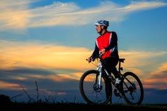 Bici de montaña adulta joven del montar a caballo del ciclista en el campo Fotografía de archivo libre de regalías