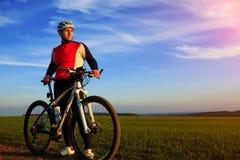 Bici de montaña adulta joven del montar a caballo del ciclista en el campo Foto de archivo libre de regalías
