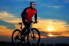 Bici de montaña adulta joven del montar a caballo del ciclista en el campo Imágenes de archivo libres de regalías