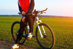 Bici de montaña adulta joven del montar a caballo del ciclista en el campo Imagen de archivo