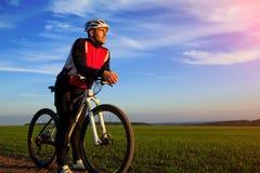 Bici de montaña adulta joven del montar a caballo del ciclista en el campo Fotos de archivo