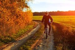 Bici de montaña adulta joven del montar a caballo del ciclista en el campo Fotos de archivo libres de regalías