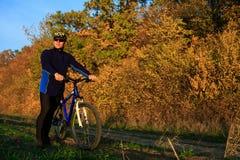 Bici de montaña adulta joven del montar a caballo del ciclista en el campo Fotografía de archivo