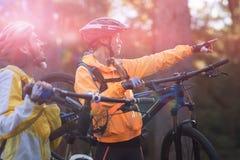 Bici de montaña de los pares del motorista que lleva y el señalar en distancia Foto de archivo