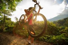 Bici de montaña del ciclista que lleva que sube en rastro del bosque del verano Imagen de archivo