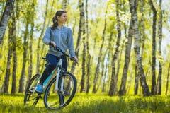 Bici de montaña del montar a caballo del ciclista en el bosque del abedul Foto de archivo
