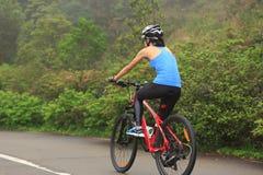 bici de montaña del montar a caballo del ciclista de la mujer en rastro Imágenes de archivo libres de regalías