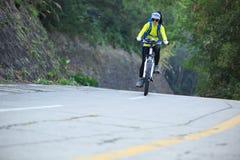 Bici de montaña del montar a caballo del ciclista de la mujer en rastro del bosque Imágenes de archivo libres de regalías