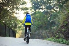 Bici de montaña del montar a caballo del ciclista de la mujer en rastro del bosque Fotografía de archivo libre de regalías