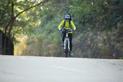 Bici de montaña del montar a caballo del ciclista de la mujer en rastro del bosque Foto de archivo