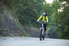 Bici de montaña del montar a caballo del ciclista de la mujer en rastro del bosque Imagen de archivo libre de regalías