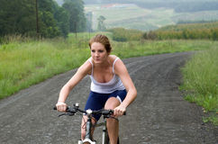 Bici de montaña del montar a caballo de la muchacha a través del bosque Fotos de archivo libres de regalías