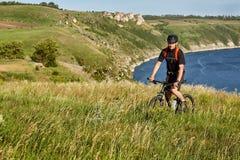 Bici de montaña del montar a caballo del hombre joven en el prado verde sobre el río azul en el campo Fotografía de archivo