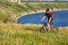 Bici de montaña del montar a caballo del hombre joven en el prado verde sobre el río azul en el campo Imagen de archivo