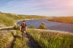 Bici de montaña del montar a caballo del hombre joven en el prado verde sobre el río azul en el campo Fotos de archivo libres de regalías