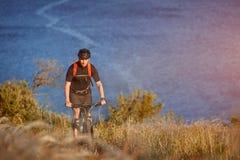 Bici de montaña del montar a caballo del hombre joven en el prado verde sobre el río azul en el campo Foto de archivo