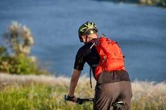 Bici de montaña del montar a caballo del hombre joven en el prado verde sobre el río azul en el campo Fotos de archivo