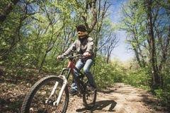 Bici de montaña del paseo del hombre a través del bosque Fotos de archivo