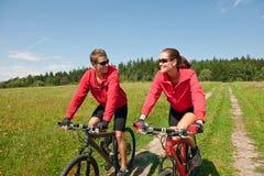 Bici de montaña feliz del montar a caballo del hombre y de la mujer Fotos de archivo