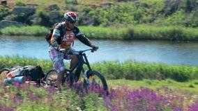 Bici de montaña masculina del montar a caballo del viajero a lo largo del río almacen de metraje de vídeo