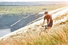Bici de montaña rirding del ciclista atractivo sobre el río hermoso en el campo en el campo Fotos de archivo