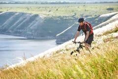 Bici de montaña rirding del ciclista atractivo sobre el río hermoso en el campo en el campo Imágenes de archivo libres de regalías