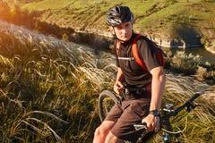 Bici de montaña rirding del ciclista atractivo sobre el río hermoso en el campo en el campo Fotos de archivo libres de regalías