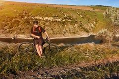Bici de montaña rirding del ciclista atractivo sobre el río hermoso en el campo en el campo Foto de archivo