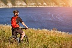 Bici de montaña rirding del ciclista atractivo sobre el río hermoso en el campo en el campo Foto de archivo libre de regalías