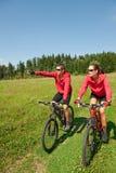 Bici de montaña juguetona del montar a caballo de los pares en prado Fotografía de archivo