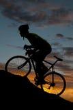 Bici del camino de la silueta cuesta arriba Imágenes de archivo libres de regalías