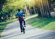 bici del montar a caballo del ciclista en parque tropical de la primavera Fotografía de archivo