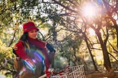Bici del montar a caballo de la muchacha en el parque en temporada de otoño soleada Fotos de archivo