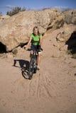 Bici del montar a caballo de la mujer en arena Foto de archivo