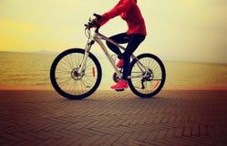 bici del montar a caballo de la mujer en la playa Fotos de archivo