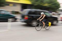 Bici del montar a caballo de la mujer en una calle borrosa Foto de archivo libre de regalías