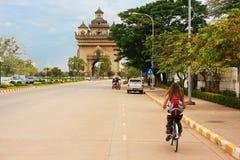 Bici del montar a caballo de la mujer joven cerca de Victory Gate Patuxai Fotografía de archivo libre de regalías
