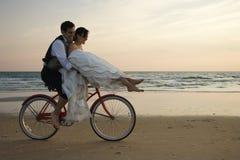 Bici del montar a caballo de los pares en la playa Imágenes de archivo libres de regalías