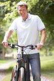 Bici del montar a caballo del hombre joven en campo Imagen de archivo libre de regalías