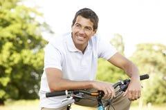 Bici del montar a caballo del hombre joven en campo Imágenes de archivo libres de regalías