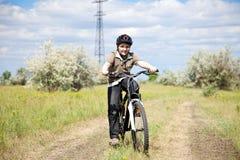 Bici del montar a caballo del muchacho en un casco Imagen de archivo libre de regalías