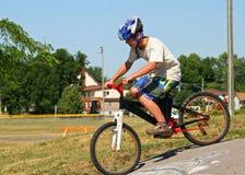 Bici del montar a caballo del muchacho en una calzada pavimentada Fotografía de archivo libre de regalías